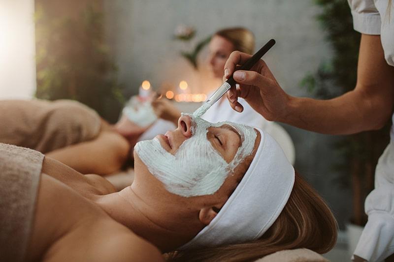 Aestheticians applying facial mask