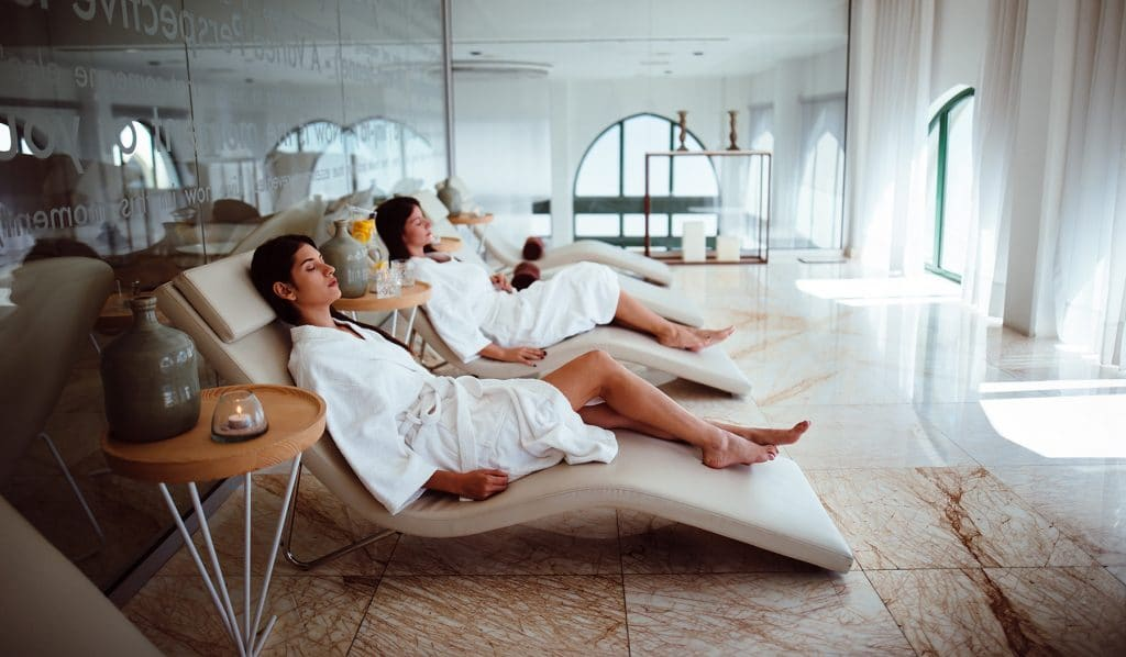 Young women in white robes relaxing at medspa